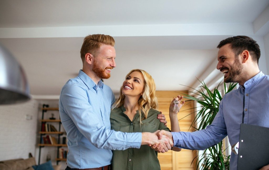 a couple shaking hands with estate agent in their home