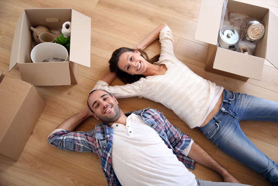 a couple laying on the floor with moving boxes